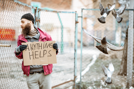 Portrait of a depressed homeless beggar standing with social message on the cardboard near the old fence outdoors
