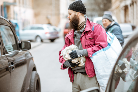 Portrait of a homeless beggar standing with bags between cars on the steret in the city. Concept of poverty Stock Photo