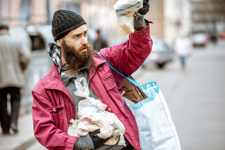 Portrait of a homeless bearded beggar standing with bag and some finded food near the trash containers in the city. Concept of poverty 写真素材