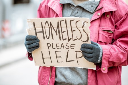 Portrait of a homeless beggar standing on the street with social message on the cardboard. Close-up on a message