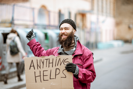 Portrait of a smiling homeless beggar standing on the street with social message on the cardboard. Concept of human poverty