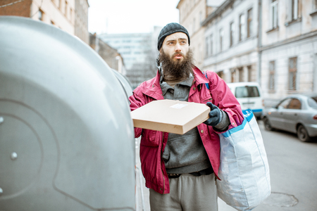 Homeless bearded beggar searching some food, rummaging in the trash in the city. Concept of poverty and unemployment