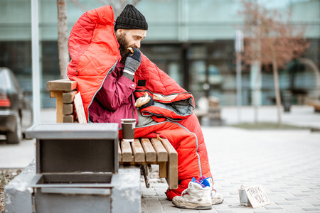 Depressed homeless beggar eating bread while sitting wrapped with sleeping bag on the bench near the business center Imagens