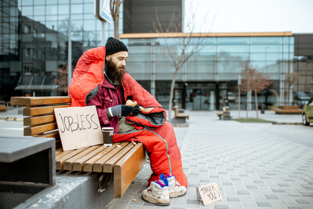 Depressed homeless beggar eating bread while sitting wrapped with sleeping bag on the bench near the business center 写真素材