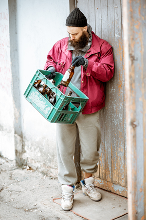 Homeless beggar bringing box with glass bottles to the collection point. Way of earning money for the poor Stock Photo