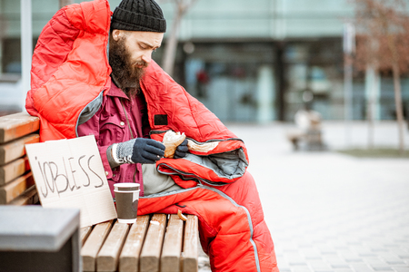 Depressed homeless beggar eating bread while sitting wrapped with sleeping bag on the bench near the business center Фото со стока