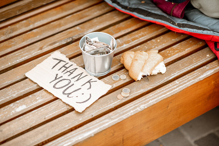 Beggars cup with thank you message and bread on the bench outdoors. Begging money concept