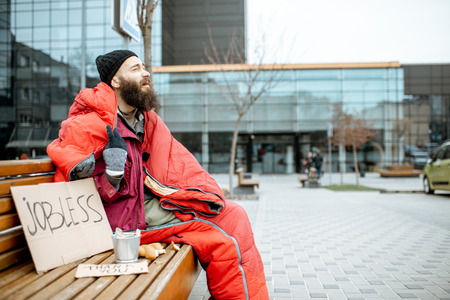 Mendigo sin hogar y desempleado sentado en el banco envuelto con saco de dormir pidiendo dinero cerca del centro de negocios