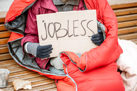 Jobless beggar with cardboard and cup begging some money, close-up view with no face