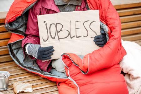 Mendigo desempleado con cartón y taza pidiendo dinero, vista cercana sin rostro Foto de archivo