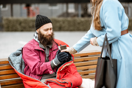 Woman helping homeless beggar giving some hot drink outdoors. Concept of helping poor people 版權商用圖片