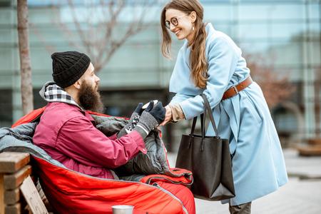 Donna sorridente che aiuta mendicante senzatetto a dare qualche bevanda calda all'aperto. Concetto di aiutare i poveri Archivio Fotografico