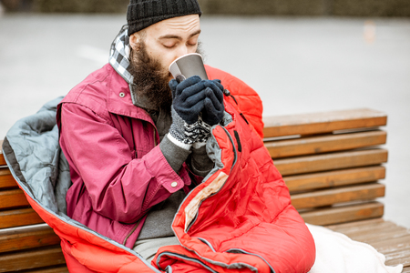 Homeless beggar enjoying hot drink sitting on the bench wrappped with sleeping bag outdoors