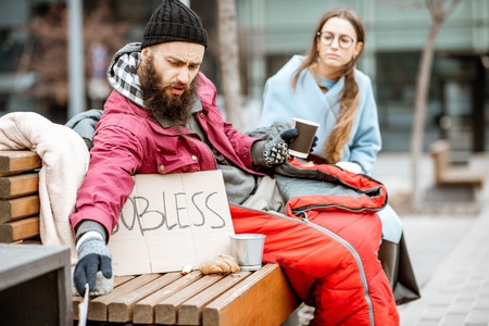 Young woman helping to a homeless beggar sitting on the bench outdoors. Concept of an understanding between poor and rich 写真素材