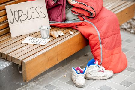 Mendigo desempleado con cartón y taza pidiendo dinero, vista cercana sin rostro