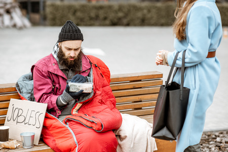 Woman helping homeless beggar giving some food outdoors. Concept of helping poor people