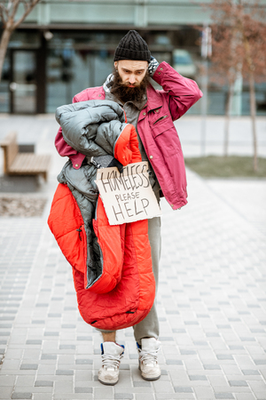 Portrait of a depressed and homeless beggar standing with sleeping bag and cardboard near the business center