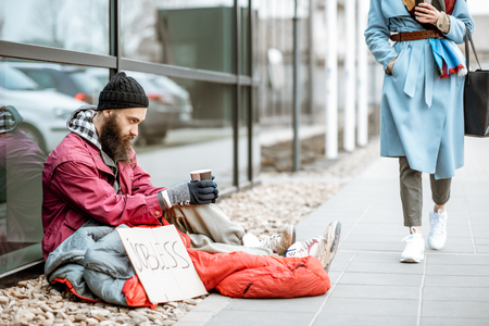 Depressed homeless begging money while sitting on the sidewalk with passing by businesswoman near the business center