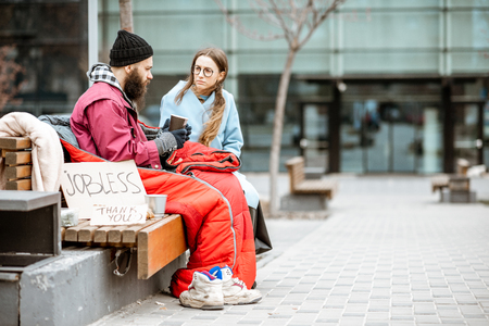 Homeless beggar with young woman listening to his sad story while sitting together on the bench outdoors. Concept of a human understanding