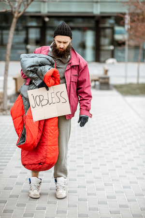 Portrait of a depressed and homeless beggar standing with sleeping bag and cardboard near the business center Foto de archivo