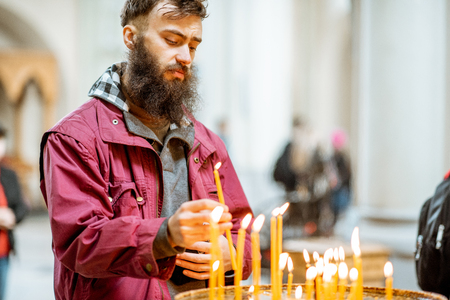 Bearded man putting candles while praying in the church