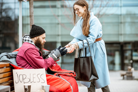 Smiling woman helping homeless beggar giving some food outdoors. Concept of helping poor people