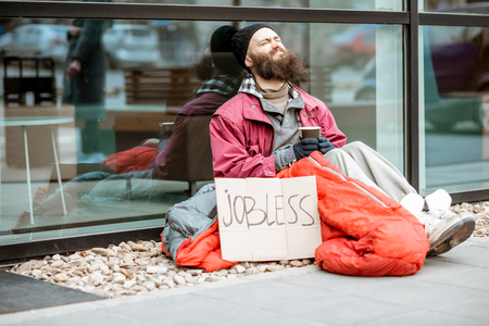 Homeless beggar wrapped with sleeping bag begging money near the business center. Concept of poverty and unemployment 写真素材