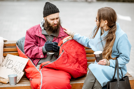 Homeless beggar with young woman listening to his sad story while sitting together on the bench outdoors. Concept of human understanding Stockfoto