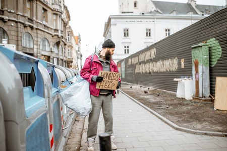 Portrait of depressed homeless beggar with cardboard begging some money on the street in the city