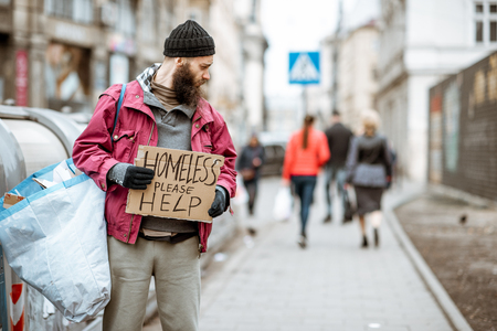 Portrait of a depressed homeless beggar with cardboard begging some money on the street in the city Banco de Imagens