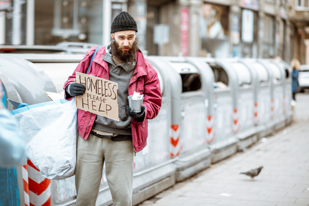 Portrait of a depressed homeless beggar with cardboard begging some money on the street in the city 版權商用圖片