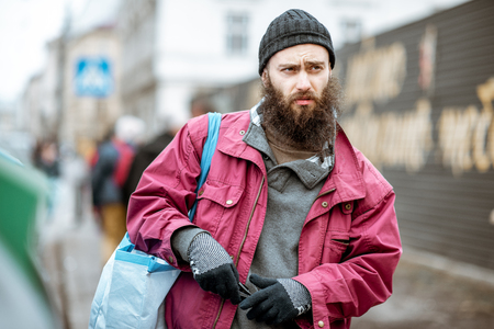 Portrait of a stylish homeless bearded beggar in the city