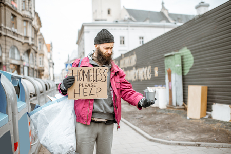 Portrait of a depressed homeless beggar with cardboard begging some money on the street in the city Stock Photo - 121320013