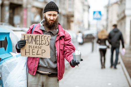 Portrait of a depressed homeless beggar with cardboard begging some money on the street in the city Stock Photo