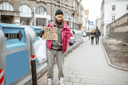 Portrait of a depressed homeless beggar with cardboard begging some money on the street in the city Stock Photo - 121319865