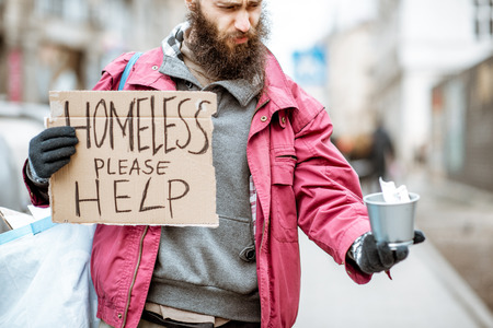 Portrait of a depressed homeless beggar with cardboard begging some money on the street in the city 写真素材