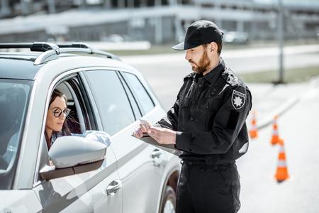 Polizist überprüft Dokumente einer jungen Fahrerin, die in der Nähe des Autos am Straßenrand in der Stadt steht Standard-Bild