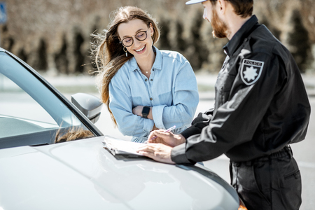 Policeman issuing a fine for violating the traffic rules to a young woman driver while standing near the car on the roadside