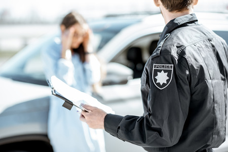 Un policier a infligé une amende pour avoir enfreint les règles de circulation à une jeune conductrice contrariée qui se tenait près de la voiture en arrière-plan