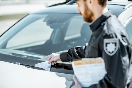 Policeman putting fine for improper parking on the windshield of the car on the roadside Stock Photo - 123767993
