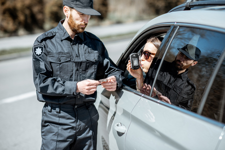 Policeman checking woman driver for alcohol intoxication with special device while stopped for violation traffic rules on the roadside Archivio Fotografico