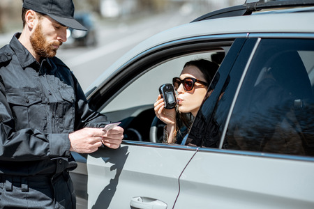 Policeman checking woman driver for alcohol intoxication with special device while stopped for violation traffic rules on the roadside Stok Fotoğraf