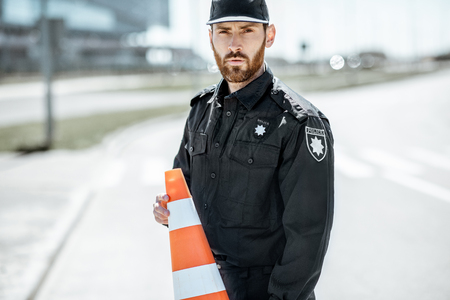 Portrait of a policeman in uniform standing with traffic cones on the city road