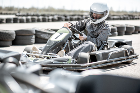 Racer in sportswear and protective helmet driving go-kart on the track Stockfoto