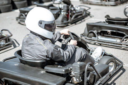 Portrait of a male racer in sportswear and protecive helmet sitting in the go-kart on the track outdoors Stockfoto