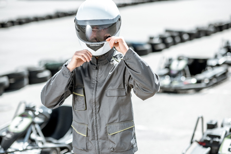 Portrait of a male racer in uniform and protective helmet standing on the track with karts on the background