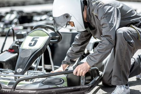 Racer or repairman in uniform serving go-kart machine before racing on the track Stock Photo