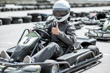 Racer in sportkleding en beschermende helm die skelter op de baan rijdt Stockfoto