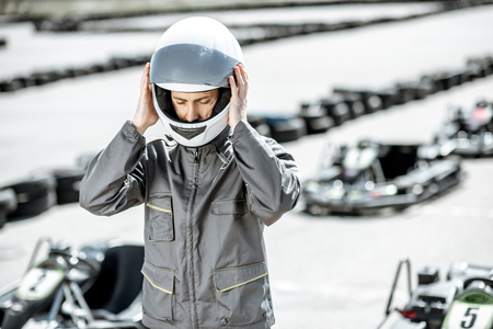 Portrait of a male racer in uniform wearing protective helmet while standing on the track with go-karts on the background