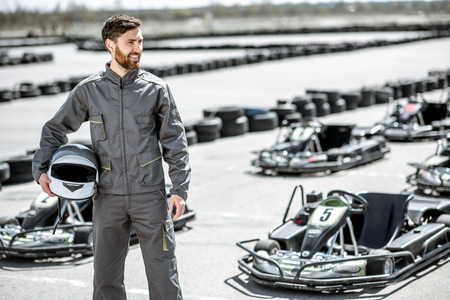 Portrait of a happy and excited racer in sportswear standing on the track with go-karts outdoors